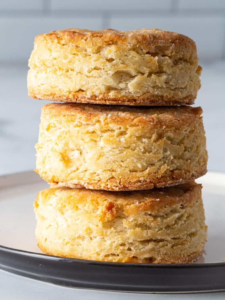 Three gluten-free biscuits stacked on a plate.