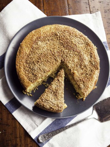 Almond flour coffee cake on plate. One slice is cut from the cake.