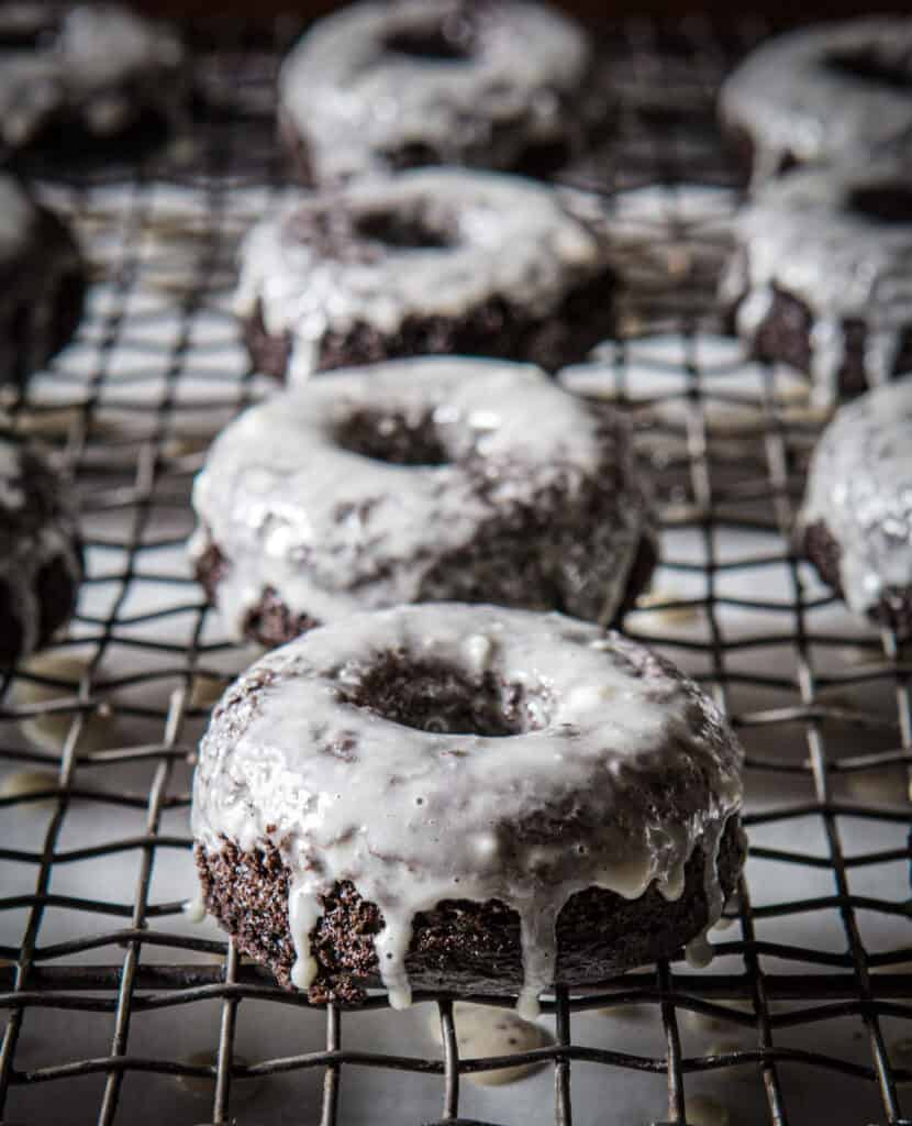 Glazed grain-free chocolate doughnuts on a cooling rack.