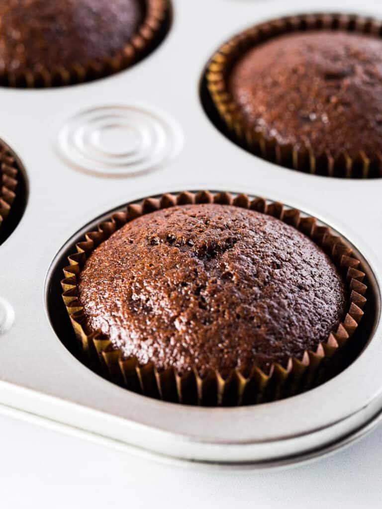 Baked gluten-free chocolate cupcake in cupcake pan.