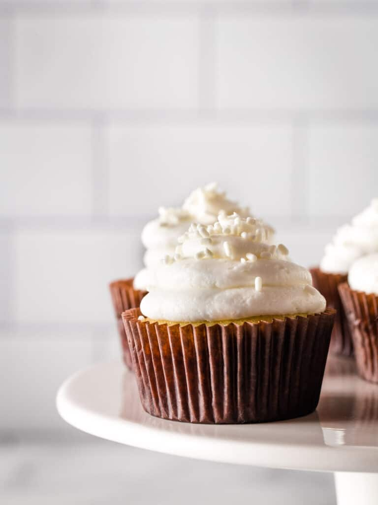 Gluten-free vanilla cupcakes with white frosting on a cake platter.