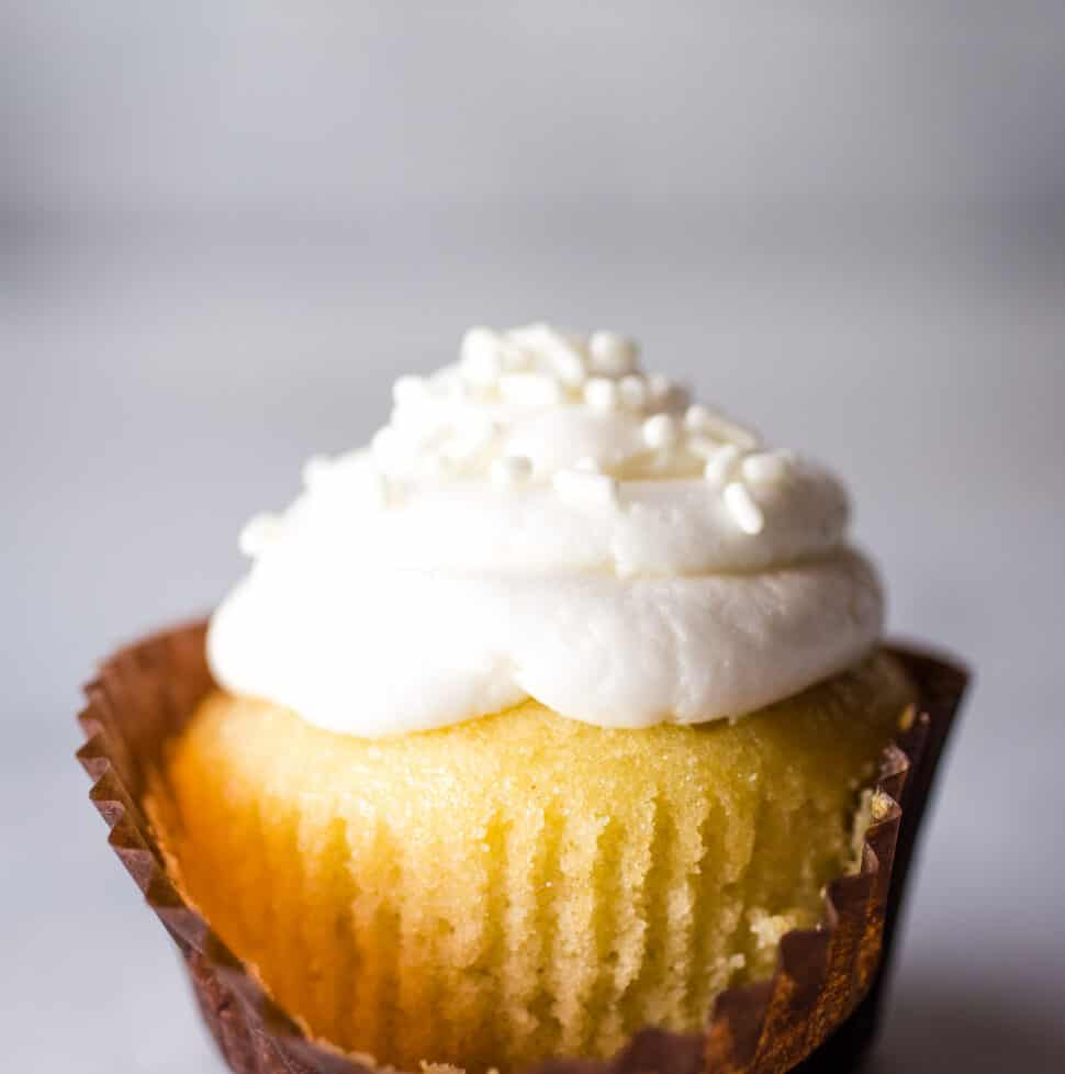 Gluten-Free vanilla cupcake. White frosting. Unwrapped in front.