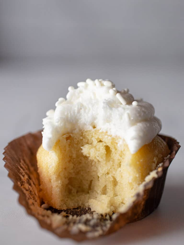 Gluten-free vanilla cupcake. Frosted with vanilla frosting. Bite taken out.