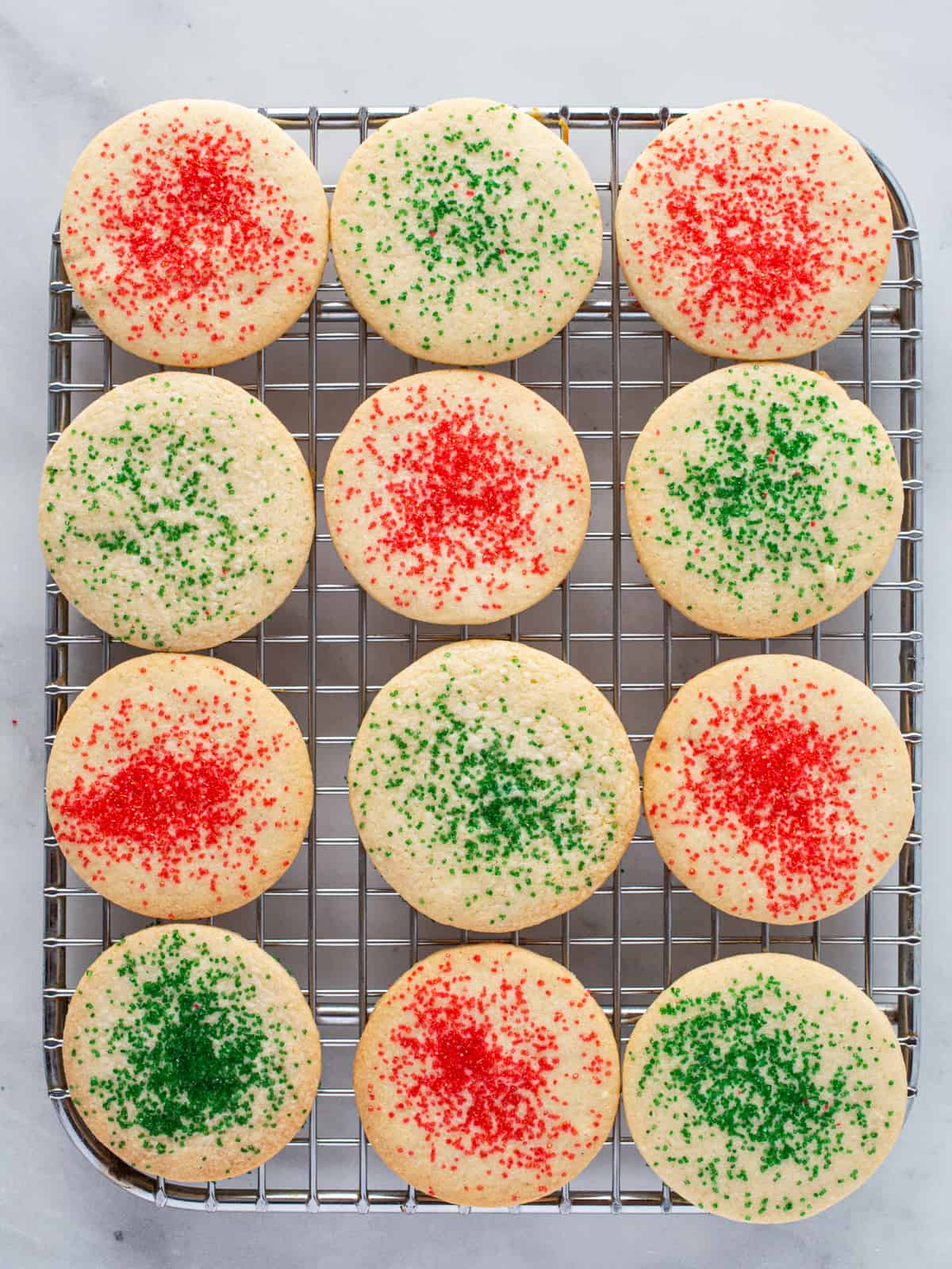 Gluten-free sugar cookies on a wire rack with red and green sugar.