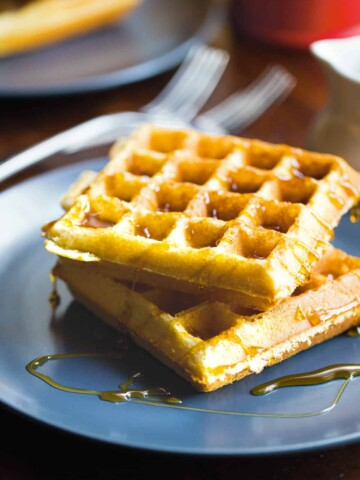 Two almond flour waffles on a plate with syrup.