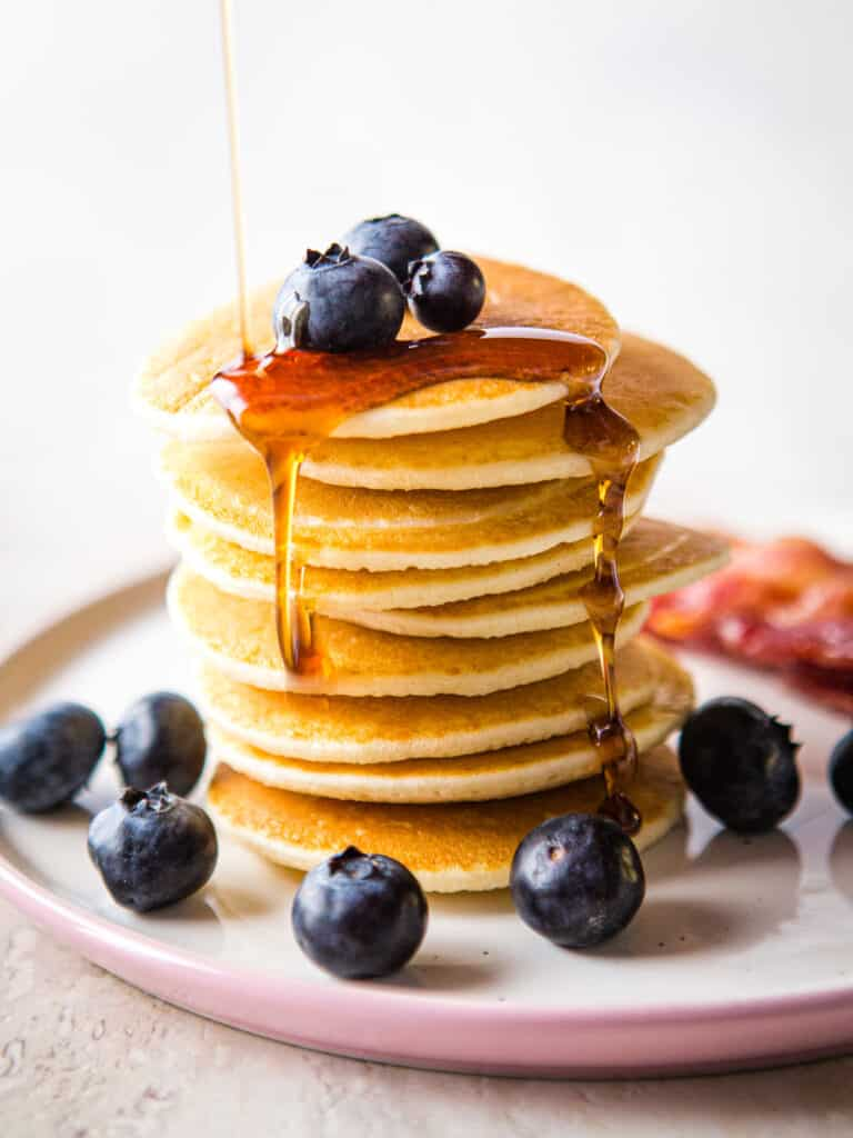Stack of coconut flour pancakes topped with blueberries and maple syrup on a small pink plate.