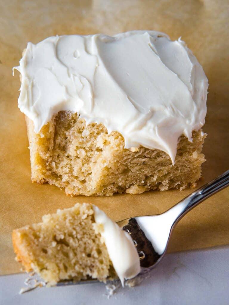 Slice of gluten-free banana cake with cream cheese icing.